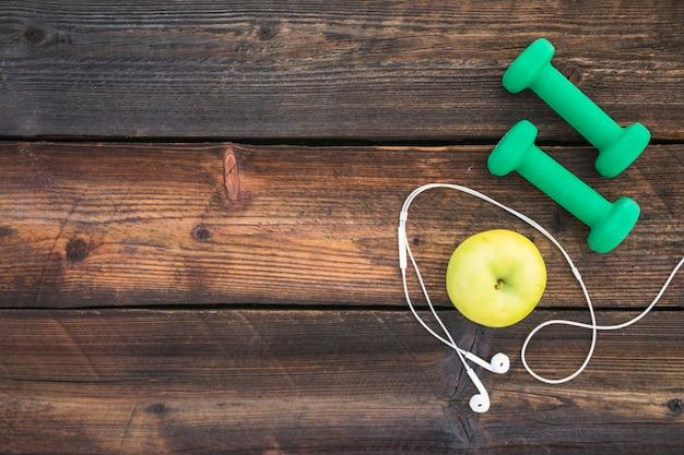Halteres verdes; fone de ouvido de maçã e branco na prancha de madeira Foto gratuita