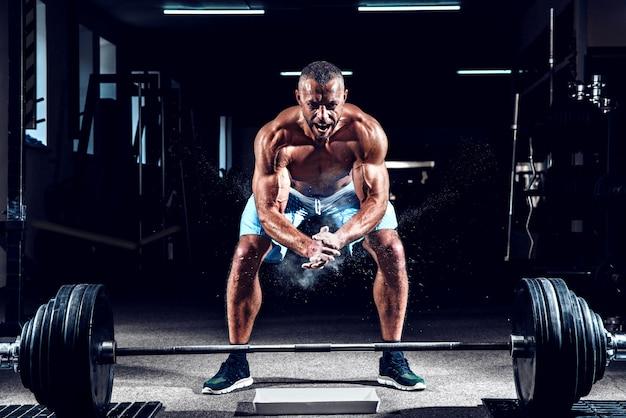 Halterofilista muscular batendo palmas de mãos e se preparando para o treino em uma academia Foto Premium