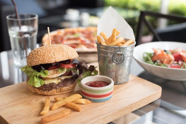 Hamburger em uma placa de madeira com batatas fritas Foto gratuita