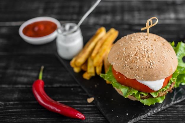 Hamburger saboroso com carne e vegetais contra um fundo escuro. comida rápida. pode ser usado como pano de fundo Foto Premium
