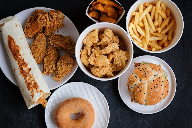 Hambúrguer, batatas fritas, donut, nuggets e chocolate em preto Foto Premium