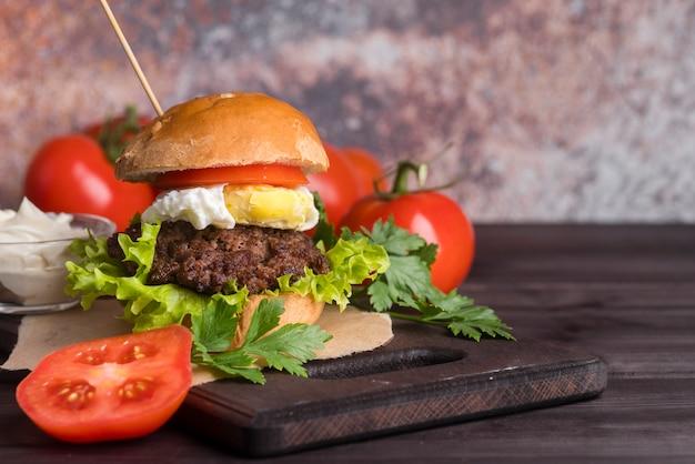 Hambúrguer caseiro com deliciosos tomates Foto gratuita