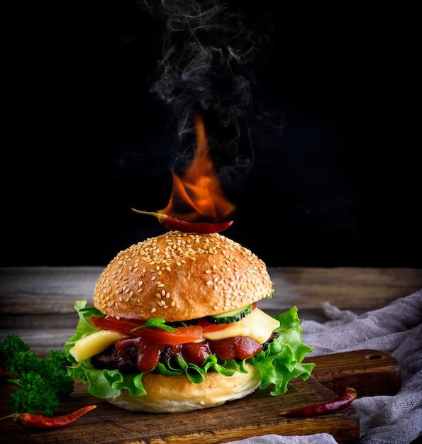Hambúrguer clássico com uma almôndega, queijo e legumes, em cima de um pão com um gergelim é uma pimenta vermelha ardente Foto Premium