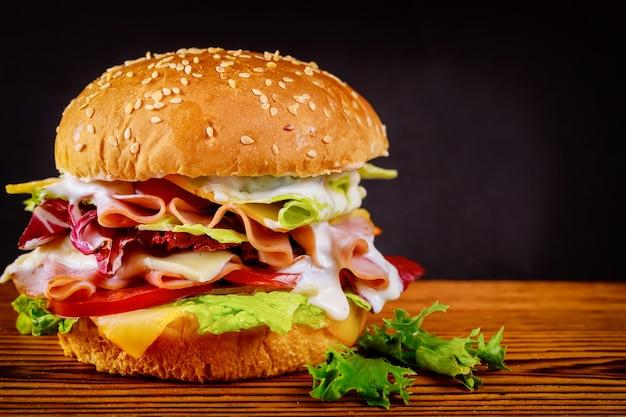 Hambúrguer com alface, queijo, presunto e tomate na superfície escura Foto Premium