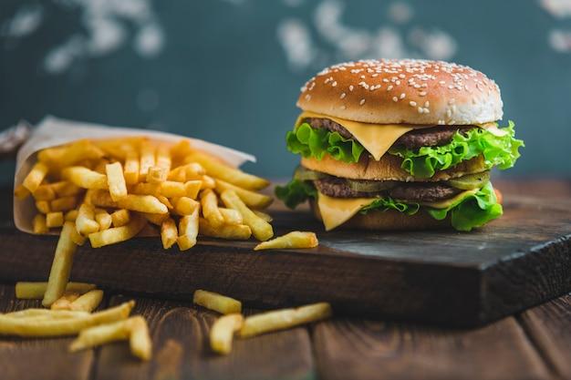 Hambúrguer com batatas e cerveja escura em uma placa de madeira sobre um fundo azul-acinzentado Foto Premium