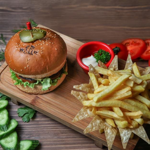 Hambúrguer com batatas fritas, pepino, tomate e molho Foto gratuita
