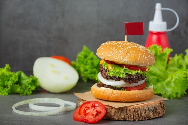 Hambúrguer com carne frita, tomate, picles, alface e queijo. Foto gratuita