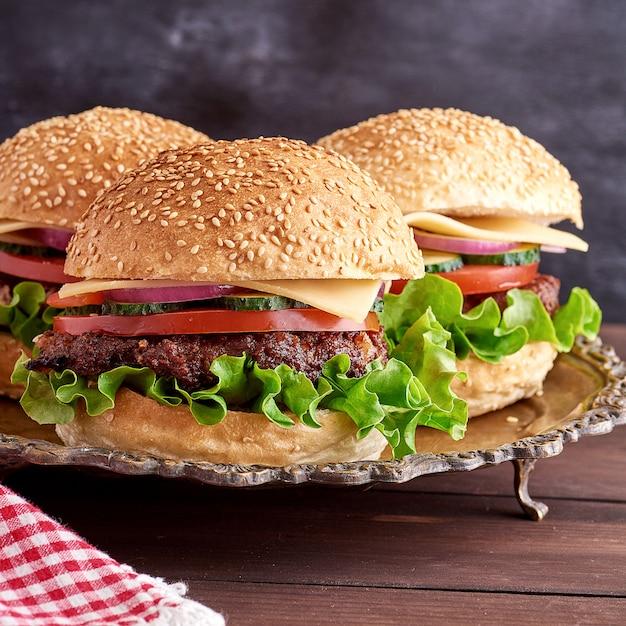 Hambúrguer com costeleta frita, queijo e legumes em um pão redondo de farinha de trigo Foto Premium