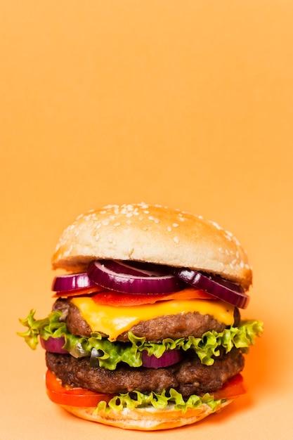 Hambúrguer com espaço de cópia em fundo amarelo Foto gratuita