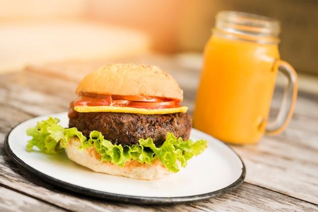 Hamburguer com tomates; queijo e alface servido com copo de suco na mesa de madeira Foto gratuita