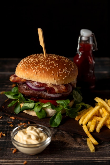 Hambúrguer de ângulo alto e batatas fritas com molhos na mesa Foto Premium