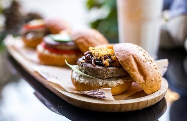 Hambúrguer de carne de vista lateral com cebola frita Foto gratuita