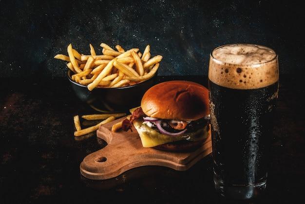 Hambúrguer de carne e queijo fresco com batatas fritas e copo de cerveja de gengibre escuro, em azul escuro, Foto Premium
