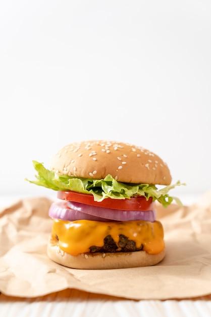 Hambúrguer de carne fresca saborosa com queijo e batatas fritas Foto Premium