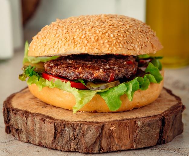 Hambúrguer de carne grande na placa de madeira Foto gratuita