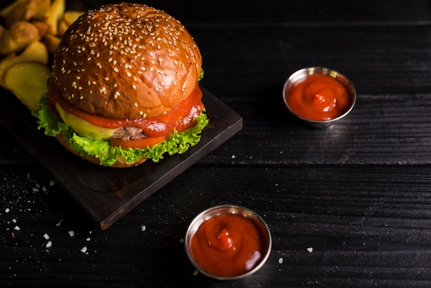 Hambúrguer de carne saborosa de alto ângulo com mergulho Foto gratuita