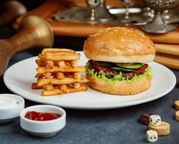 Hambúrguer de carne servido com batata frita, maionese e ketchup Foto gratuita