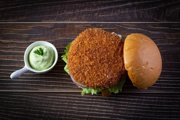Hambúrguer de frango com alface, tomate, cebola roxa e maionese artesanal na mesa de madeira. delicioso. Foto Premium