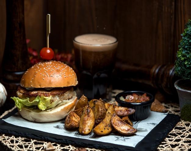 Hambúrguer de frango com batata frita caseira de lado Foto gratuita