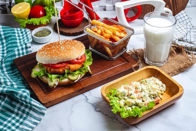 Hambúrguer de frango com batatas fritas em uma placa uma salada de capital e um copo de iogurte Foto gratuita