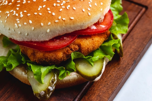 Hambúrguer de frango de vista lateral com fatias de tomate e alface no quadro Foto gratuita
