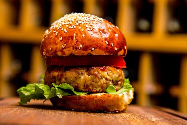 Hambúrguer de frango na vista lateral da placa de madeira Foto gratuita