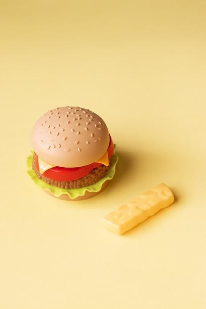 Hambúrguer de plástico, salada, tomate, sobre um fundo amarelo Foto Premium