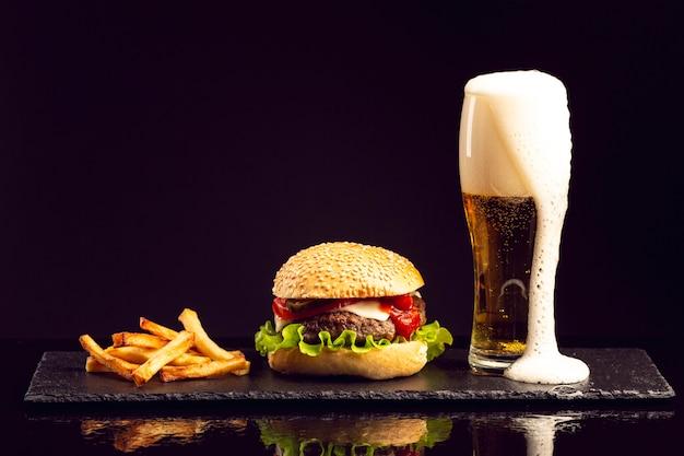Hambúrguer de vista frontal com batatas fritas e cerveja Foto gratuita