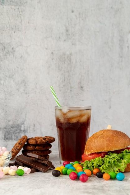 Hambúrguer de vista frontal com doces Foto gratuita