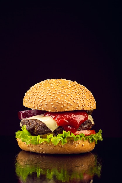 Hambúrguer de vista frontal com fundo preto Foto gratuita