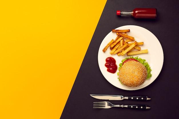 Hambúrguer de vista superior com batatas fritas com espaço de cópia Foto gratuita