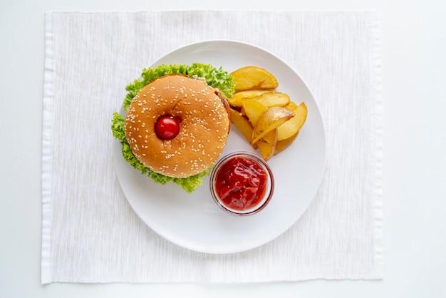 Hambúrguer de vista superior com batatas fritas no prato Foto gratuita