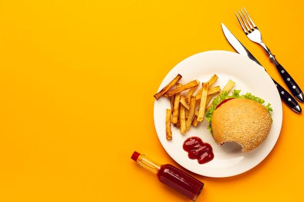 Hambúrguer de vista superior com batatas fritas num prato Foto gratuita