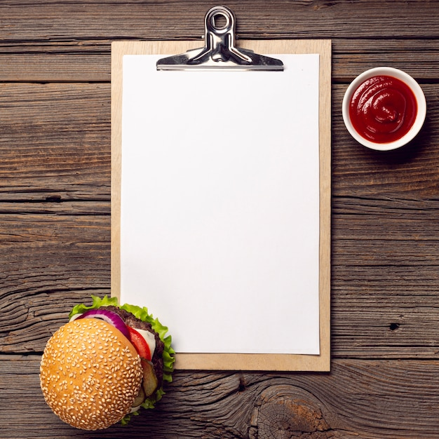 Hambúrguer de vista superior com prancheta de mock-up Foto gratuita
