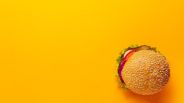Hambúrguer de vista superior em fundo laranja Foto gratuita