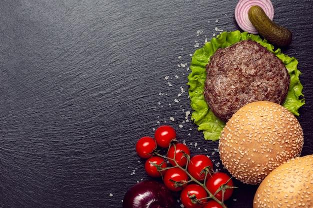 Hambúrguer de vista superior em fundo preto Foto gratuita
