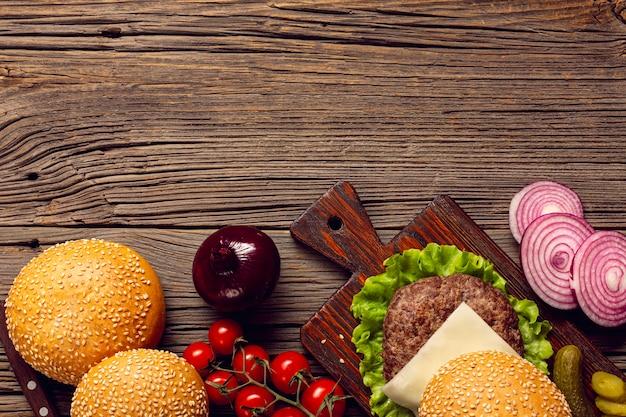 Hambúrguer de vista superior na mesa de madeira Foto gratuita