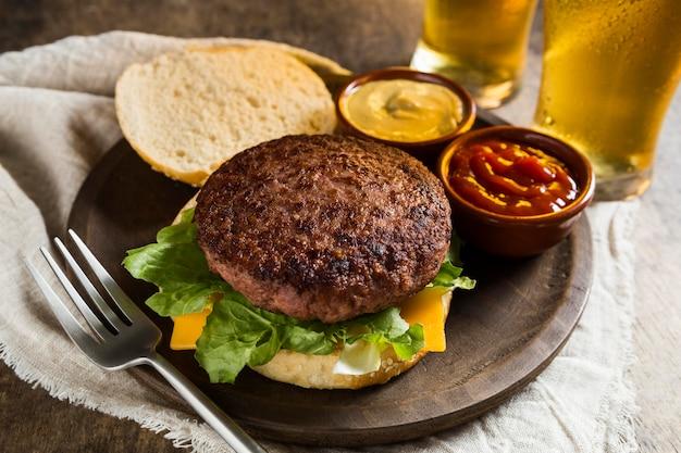 Hambúrguer delicioso com copos de cerveja e ketchup Foto Premium