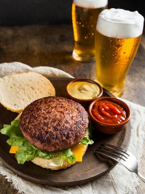 Hambúrguer delicioso com copos de cerveja e molho Foto Premium
