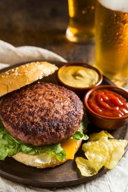 Hambúrguer delicioso com copos de cerveja e mostarda Foto Premium