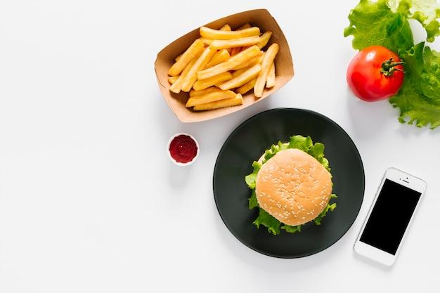 Hambúrguer e batatas fritas na chapa com copyspace Foto gratuita