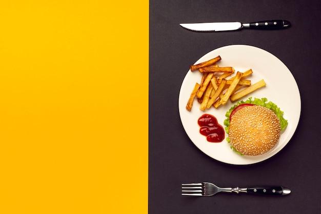 Hambúrguer e batatas fritas na chapa com espaço de cópia Foto gratuita