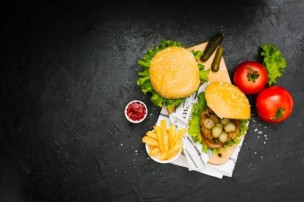 Hambúrguer e batatas fritas na placa de madeira com copyspace Foto gratuita