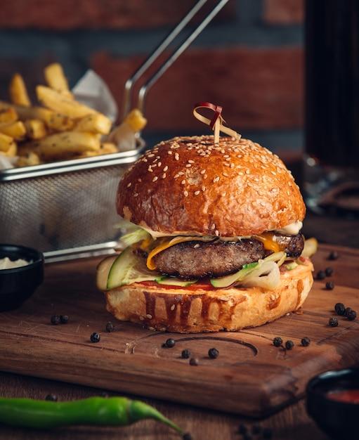 Hambúrguer enorme com carne frita e legumes Foto gratuita