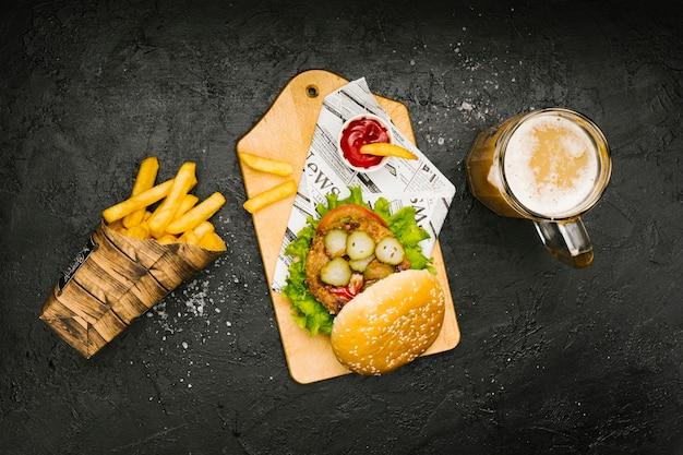 Hamburguer flat-lay na placa de madeira com batatas fritas e cerveja Foto gratuita