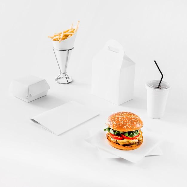 Hamburguer fresco; batatas fritas; pacotes e copo de eliminação em fundo branco Foto gratuita