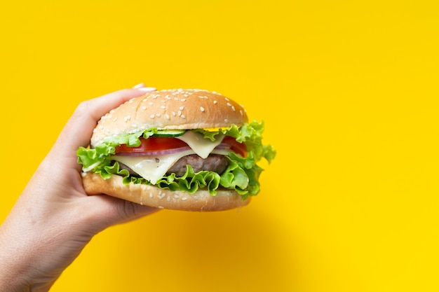 Hambúrguer na frente de fundo amarelo Foto gratuita