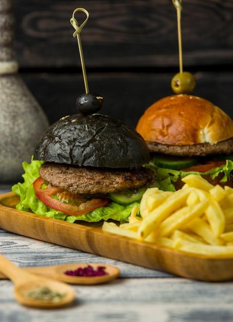 Hambúrguer preto e branco com batatas fritas em bandeja de madeira Foto gratuita
