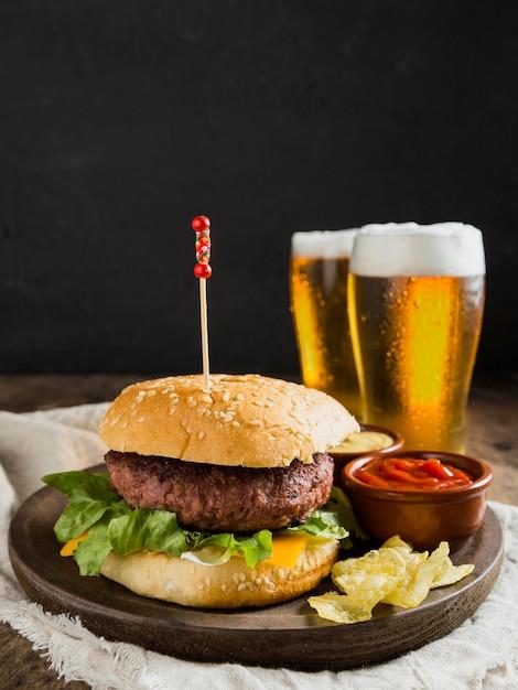 Hambúrguer saboroso com copos de cerveja e batatas fritas Foto Premium