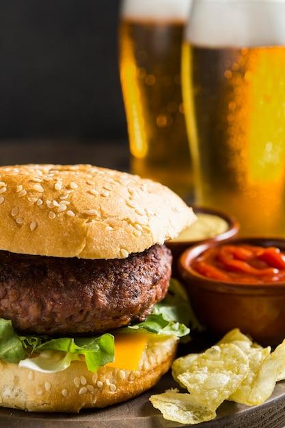 Hambúrguer saboroso com copos de cerveja e ketchup Foto Premium